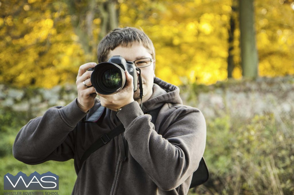 Man taking picture in the autumn park